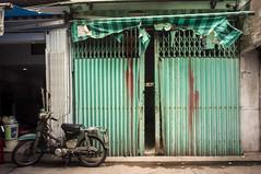 (kuuan) Tags: voigtländerheliarf4515mm manualfocus mf voigtländer15mm aspherical f4515mm superwideheliar apsc sonynex5n saigon hcmc vietnam market gate colorful green motorbike shopfront foldingdoor foldinggate hondacub chợphúnhuận phunhuanmarket emptyshop closedshutter