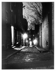 4x5-115p-58 (ndpa / s. lundeen, archivist) Tags: nick dewolf nickdewolf december bw blackwhite photographbynickdewolf boston massachusetts beaconhill 1950s film 4x5 largeformat sheetfilm monochrome blackandwhite night nighttime lights trees branches cobblestone street manholecover building buildings shadow light shadows alley acornstreet positive 1957