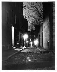 4x5-114bp-58 (ndpa / s. lundeen, archivist) Tags: nick dewolf nickdewolf december bw blackwhite photographbynickdewolf boston massachusetts beaconhill 1950s film 4x5 largeformat sheetfilm monochrome blackandwhite night nighttime lights trees branches cobblestone street manholecover building buildings shadow light shadows alley acornstreet positive 1957