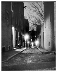 4x5-114ap-58 (ndpa / s. lundeen, archivist) Tags: nick dewolf nickdewolf december bw blackwhite photographbynickdewolf boston massachusetts beaconhill 1950s film 4x5 largeformat sheetfilm monochrome blackandwhite night nighttime lights trees branches cobblestone street manholecover building buildings shadow light shadows alley acornstreet positive 1957