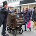 Kölner Drehorgelspieler bekommt eine Spende einer Frau in der Fußgängerzone