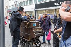 Schwarz gekleideter Drehorgelkünstler in der Kölner Fußgängerzone