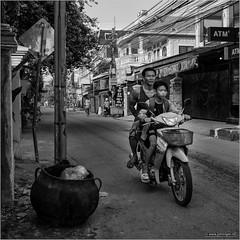Siem Reap street (John Riper) Tags: johnriper street photography straatfotografie square vierkant bw black white zwartwit mono monochrome candid john riper xt3 fujifilm siem reap cambodia motor taxi boy man driver passenger atm pot suzuki nike