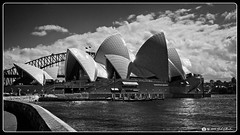 Sydney Opera House & Bridge (Bob Shrader) Tags: olympuspenf olympusmzuikodigitaled12100mmf40ispro 20mm f11 11000sec 200iso raw microfourthirds mft m43 mirrorless oceania australia newsouthwales sydney landmarks sydneyoperahouse nature water harbor sydneyharbor sky clouds structure bridge sydneyharborbridge transportation sidewalk walkway curb penf zoomlens mzuiko12100mmf40ispro olympusmzd12100mmf40ispro exterior outdoors wideshot on1 photoraw2020 blackandwhite bw blackwhite monochrome fauxfilm infraredbw highcontrast monotone photoborder photoedge photoframe postprocessing preset
