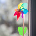 Small colorful decorative windmill in a flowerpot on the window bench