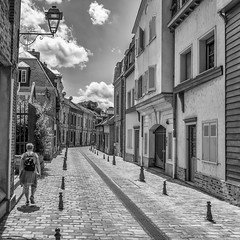 Midday sun (B&W) (stevefge) Tags: 2019 amiens france street people candid unsuspectingprotagonists unsuspecting women shadows houses clouds lamps bollards solo solitary squares blackandwhite bw monochrome zw zwartwit nikon reflectyourworld