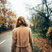 Woman walking on a road in the woods.