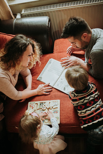 Brother and sister learning with their parents.