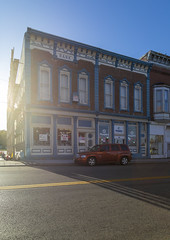 Bank — New Vienna, Ohio (Pythaglio) Tags: building structure historic commercial ornate italianate bank twostory brick sixbay storefronts 11windows cornice brackets dentils pilasters pedimented segmentalarched sidewalk street car shadows newvienna ohio clintoncounty cli2009