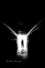 Into the light (Malcom Lang) Tags: bw white black mono light woman dark person lights pipes tunnel