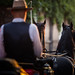 Black horses pulling a carriage with driver and passanger in blurry foreground