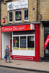 Brighouse 017 (Peter.Bartlett) Tags: fastfood shopfront unitedkingdom people facade olympuspenf westyorkshire colour peterbartlett urban candid uk m43 microfourthirds shopwindow woman sign walking streetphotography doorway brighouse england