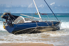 Disaster at sea. The wreck of a sailing yacht. Yacht was dropped from the anchor and thrown to the beach. Waves break the hull and fill it with water. Nai Harn Beach, Phuket, Thailand 25 October 2019