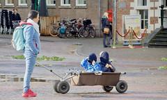 Under cover Haarlemmers (andzwe) Tags: haarlem undercover kids covered wagon wagen mother square netherlands nederland haarlemmers children panasonicdmcgh4 dutch bolderkar harlem