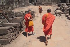 Monks On The Move (peterkelly) Tags: digital canon 6d asia southeastasia indochinaencompassed gadventures cambodia angkorwat angkor angkorthom bayontemple monk orange monks courtyard stone mahayana buddhist kingjayavarmanvii