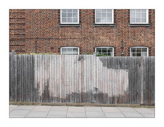 The Built Environment, North West London, England. (Joseph O'Malley64) Tags: thebuiltenvironment newtopography newtopographics manmadeenvironment manmadestructure building structure graffiti graffitiremoval beltsander northwestlondon london eng uk britain british greatbritain brickwork bricksmortar cement pointing housing homes dwellings abodes windows windowblinds curtains lintels wiring electricalwiring electricalconduit lamp lighting airbricks ornamentalbrickwork mitredbricklintels windowsills bushes vegetation fencing woodenfencepanels concrete pavement pavingslabs incline gradient architecture architecturalfeatures architecturalphotography documentaryphotography britishdocumentaryphotography fujix fujix100t accuracyprecision