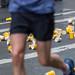 Athlet läuft an der Verpflegungsstation vorbei mit Becher auf dem Boden