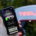 Tesla Supercharging auf einem Smartohone in der App vor einer Tesla Ladestation