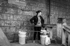 In the kitchen (Go-tea 郭天) Tags: chongqing républiquepopulairedechine kitchen nomad portable food cook cooking pole stairs steps business duty drums 2 plastic bag easy woman lady alone lonely old oil pots wall bricks bottle portrait street urban city outside outdoor people candid bw bnw black white blackwhite blackandwhite monochrome naturallight natural light asia asian china chinese canon eos 100d 24mm prime