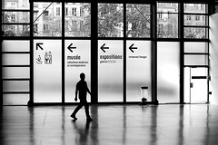 Leaving the exhibition (pascalcolin1) Tags: paris homme man museum musée reflets reflection lumière light fenetres windows portes doors arrows flèches exposition exhibition sortie exit photoderue streetview urbanarte noiretblanc blackandwhite photopascalcolin 50mm canon50mm canon