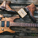 Charvel San Dimas Hawaiian koa with brown shoes and Fossil watch on a wooden table.