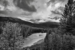 Patches of Clouds Around the Bow Range and Peaks Near the Continental Divide (Black & White, Banff National Park) (thor_mark ) Tags: albertaprovincialhighwayno1a alongbanksofbowriver atmorantscurve banffnationalpark banfflakelouisecorearea blackwhite bowrange bowriver bowvalleyparkway canadianpacificrailway canadianpacificrailwaytrack canadianrockies capturenx2edited cloudsswirlingaround cloudsacrossvalley cloudsaroundmountains colorefexpro continentaldivide day4 evergreens fairviewmountain hillsideoftrees landscape lookingwest lookingtocontinentaldivide lookingtomountainsofthecontinentaldivide lowclouds morantscurve mostlycloudy mountainvalley mountains mountainsindistance mountainsoffindistance nature nikond800e outside overcast portfolio project365 railline railroad railroadtracks railwaytracks river riverbank rockymountains saddlemountain sheolmountain silverefexpro2 southerncontinentalranges traintracks trees triptoalbertaandbritishcolumbia alberta canada