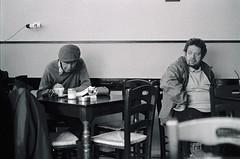 at the coffee shop (Giorgos Voulgaris) Tags: nikonem analog film kodak 400tx 135mm bw blackwhite people coffee sitting hat candid streetphotography corfu