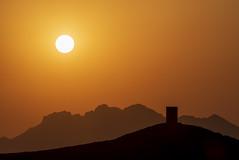 Oman, Wadi al-Muaydin (Alexander JE Bradley) Tags: 70200mmf28 afsvrzoomnikkor70200mmf28gifed nikon70200mmf28fl d500 nikkor nikon asia middleeast arabianpeninsula oman addakhiliyah birkatalmouz birkatalmouzruin oaisis wadialmuaydin ruins architecture sultanateofoman buildings fortress tower turret fort citywalls fortificationtowers landscape hill lookout haze viewpoint mountain mountains peak rock rocky scenic nature geologicalformation noperson sky nopeople backlit silhouette naturallight sunny sunset dusk alexanderjebradley photograph photography travel famousplace tourism traveldestination travelphotography wwwalexanderjebradleycom wwwaperturetourscom aperturetours omanphotographyworkshop birkatalmawz