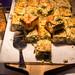 Quiche mit grünem Gemüse, Brokkoli, Spinat und Bergkäse in kleinen Stücken geschnitten