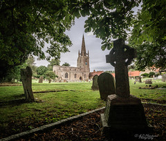 Framed (Through_Urizen) Tags: architecture bedfordshire category england external harrold places canon1585mm canon canon70d outdoor architecturephotography church churchyard headstones graves graveyard trees lawn grass sky villagechurch spire uk unitedkingdom greatbritain