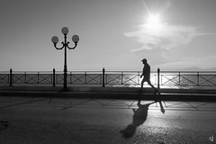 Training (tzevang.com) Tags: walking training bythesea seascape sun clouds greece piraeus promenade bw bwseascape light