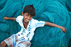 India, young boy on a fishing net (Dietmar Temps) Tags: asia beach boy culture ethnic ethnie ethnology faces fishingnet fishingvillage india indien naturallight outdoor pamban pambanbridge people rameswaram smile southasia streetphotography teeth tradition traditional 35mm
