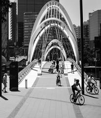 Seafarers Bridge Melbourne (laurie.g.w) Tags: seafarers bridge melbourne yarra river city bw blackandwhite bikes people buildings urban eosm mirrorless m3