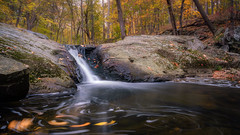 Croydon Creek Waterfall in Autumn (John Brighenti) Tags: longexposure autumn red fall water creek river waterfall rocks stream flickr boulders brook park forest outside outdoors md woods scenery maryland local croydon natures rockville ocotber landscapephotography orange brown green colors leaves yellow colorful hiking sony foliage trail alpha naturecenter a7rii wideangle nd 24mm polarizer hoya ilce7rm2 sel24f14gm
