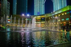 Fountains in front of Suria KLCC at night in Kuala Lumpur, Malaysia (UweBKK (α 77 on )) Tags: kuala lumpur kualalumpur malaysia southeast asia city centre urban center sony alpha 550 dslr fountain water reflection evening night suria klcc park light