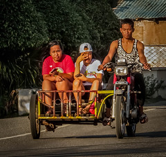 The family transport (FotoGrazio) Tags: motorbike travelphotography ilocosnorte tricycledriver wheels waynesgrazio streetscene pacificislanders people luzon travel sunintheeyes rural philippines transportation three sitting sidecar 3 pagudpud honda waynegrazio motorcycle streetphotography filipino outdoors fotograzio family tricycle street waynestevengrazio