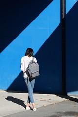 out of the blue (pix-4-2-day) Tags: blue blau licht light ray lichtstrahl diagonal diagonale girl jeans standing überkreuz gekreuzt crossed rucksack backpack mädchen stehend shadow schatten lines linien