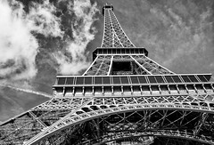The Eiffel Tower - it's not Blackpool :-) (Katrina Wright) Tags: france paris dsc5616edit eiffeltower monochrome bw sky clouds metal structure pattern line geometry architecture wroughtiron lattice fence hmbt hff hss sliderssunday fencefriday
