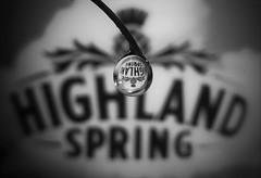 Highland Spring Water..x (Lisa@Lethen) Tags: macromondays brandandlogos highlandspring scottish water bottled bottle droplet refraction macro bw blackandwhite mono