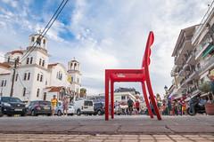 Roter Stuhl am Marktplatz in einer griechischen Stadt