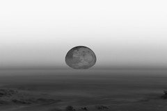 Partially Squished Moon on the Horizon, variant (sjrankin) Tags: 4november2019 edited nasa iss iss060 iss060e36431 horizon clouds haze distorted moon grayscale