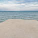A view of the sea and cloudy sky from a concrete plattform. Lifeless minimalist seascape