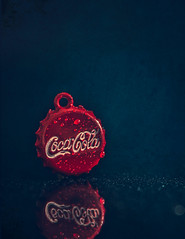Coca Cola mini charm (Ro Cafe) Tags: cocacola mm nikkor105mmf28 nikond600 macromondays brandandlogos red macro reflections miniature drops charm blue darkmood
