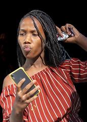 Portrait (D80_544457) (Itzick) Tags: manhattansep2019 nyc blackbackground blackwoman face facialexpression cellphone streetphotography portrait candid color colorportrait hairstyle d800 itzick