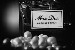 What a girl needs... (Ageeth van Geest) Tags: macromondays perfume missdior pearls bw blackandwhite monochrome zwartwit fragance parfum brandandlogos logo glow