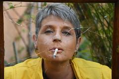 DSC_1331 (griecocathy) Tags: portrait visage vitre brisée cigarette végétations cadre fumer jaune vert beige cathy