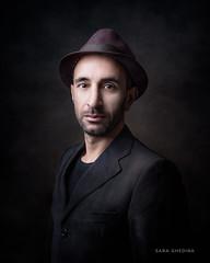 Man with Purple Hat (saraghedina) Tags: oldmaster tshirt suit italian formalwear 50mm canon fineart vertical oneperson darkbackground rembrandtlight chiaroscuro hat portrait man