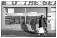 Taste o' the Sea (Nodding Pig) Tags: bridlington yorkshire eastriding england greatbritain uk 2019 seaside fish shop passersby film scan monochrome negative 35mm ilford fp4 nikonfm2 nikkor50mmlens 20190209023101border tasteothesea
