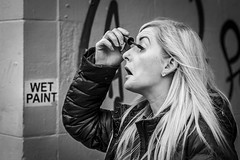 Wet Paint (Leanne Boulton) Tags: urban street candid portrait portraiture profile streetphotography candidstreetphotography candidportrait streetportrait streetlife decisivemoment woman female face expression emotion mood feeling eyes makeup mascara wetpaint sign paint juxtaposition fun funny humour humorous timing blonde hair cosmetics tone texture detail depthoffield photography naturallight outdoor light shade alley alleyway city scene human life living humanity society culture lifestyle fashion canon canon5dmkiii 70mm ef2470mmf28liiusm black white blackwhite bw mono blackandwhite monochrome glasgow scotland uk