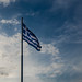 Greek flag flying low and a dramatic sky in the background